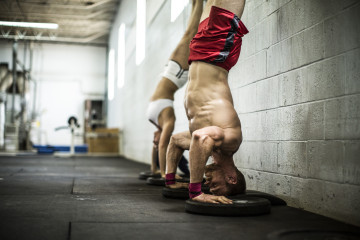 man and woman doing handstand pushups