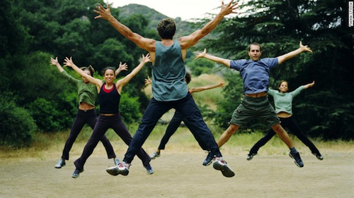 Group of people doing jumping jacks in the woods