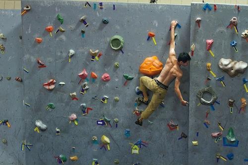 Shirtless man rock climbing