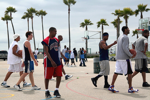 Men playing basketball outside