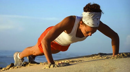 Girl doing push ups on the beach