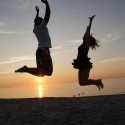 Two people jumping on a sunset beach - Image courtesy of Flickr user Click E